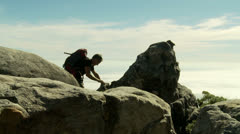 Rock climber with backpack reaches top of mountain Stock Footage