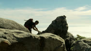Stock Video Footage of Rock climber with backpack reaches top of mountain