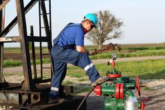 Oil worker with wrench check pipeline Stock Photos