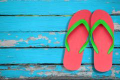 Red and green flip flop sandals on blue wood Stock Photos