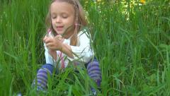 Happy Little Girl Singing while Playing with Grass, Child in Park, Children Stock Footage