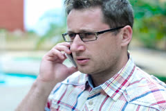 Young man in tourist resort talking on cellphone, steadicam shot Stock Footage