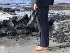 Businessman without shoes standing on stony beach, slow motion shot at 60fps Stock Footage