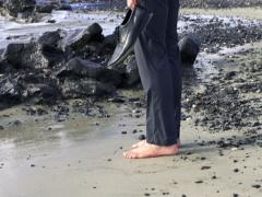 Businessman without shoes standing on stony beach, slow motion shot at 240fps Stock Footage