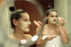 Young woman applying face mask in front of mirror Stock Footage