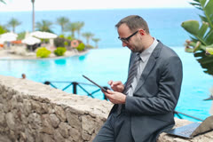 Portrait of smiling businessman using electronics in touristic resort, steadicam Stock Footage