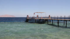 People Swimming Around Jetty in Red Sea Stock Footage