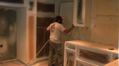 WORKER SPRAY PAINTING KITCHEN - stock footage