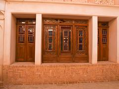 the exterior of stain glass wooden doors in historic old house in kashan, ira - stock photo