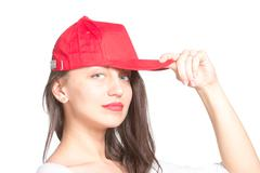 attractive young woman wearing a red baseball cap - stock photo