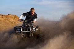 Teen on quad ATV kicking up dust - stock photo