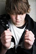 Teen crime - kid in handcuffs Stock Photos