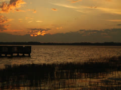 Sunset sky over lake horizon dock grass foreground wider - stock footage