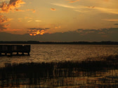 Stock Video Footage of Sunset sky over lake horizon dock grass foreground wider