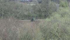 Seabirds scavenge near tractor tilling field. - stock footage