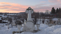 Cross, cemetery, church at sunset during winter time - stock footage