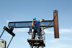 oil worker talking on mobile phone - stock photo
