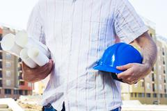 Construction worker holding project and blue hard hat Stock Photos