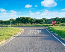 Country road with stop sign Stock Photos