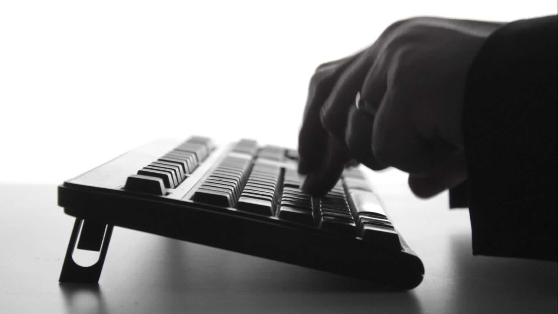 Silhouette of man typing on computer keyboard ~ Footage ...