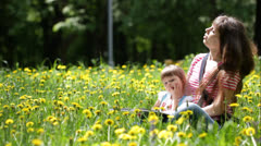 Young mother and her daughter having fun outdoors - stock footage