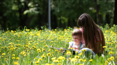 Young mother and her daughter read a children's book outdoors Stock Footage
