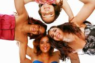 Stock Photo of group of happy women standing in huddle, smiling, low ange view.