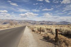 Yksinäinen tie suuri autiomaa Kuvituskuvat