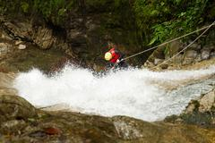 Stock Photo of Adult Woman Wearing Waterproof Equipment Descending A Waterfall