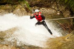 Stock Photo of Adult Man Wearing Waterproof Equipment Descending A Waterfall