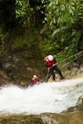 Stock Photo of Team Of Two Young Women Wearing Waterproof Equipment Descending A Waterfall