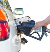 hand holding a nozzle while fueling white car. focus on the nozzle - stock photo