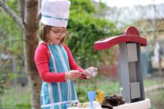 Little girl playing cooking Stock Photos