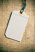 blank price tag label on burlap background - stock photo