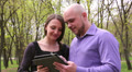 man and a woman watching photos on a tablet 1 Footage