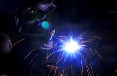 industrial worker make a spark by welding - stock photo