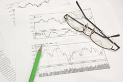 stock graphs, pencil and glasses - stock photo