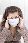 The sick girl with medical mask with sad eyes Stock Photos