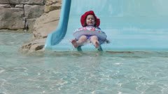 Girl goes down slide a resort Stock Footage