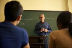 school people, professor talking to students during lesson in college - stock photo
