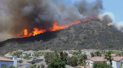 BRUSH FIRE THREATENS HOMES - stock footage