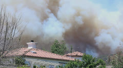 BRUSH FIRE LOOMS ABOVE HOME - stock footage