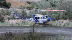 FIRE COPTER TAKES OFF TO BATTLE BRUSH FIRE Stock Footage