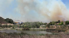 COPTER REFILLS TO FIGHT FIRES WIDE Stock Footage