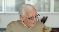 Close up of senior Caucasian man eating vegetables Stock Footage