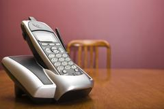 Cordless phone on a table with chair in the background Stock Photos