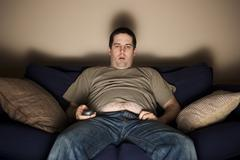 Overweight slob watching tv Stock Photos