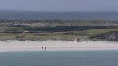 Walkers on beach at bay, Connemara, Ireland + zoom out Atlantic coast Stock Footage
