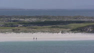 Stock Video Footage of Walkers on beach at bay, Connemara, Ireland + zoom out Atlantic coast