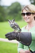 woman with a southern white-faced owl on her falconry glove - stock photo